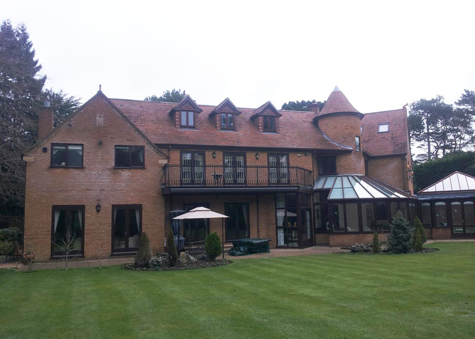 A photograph of a property with added roof dormers and a stairwell tower.